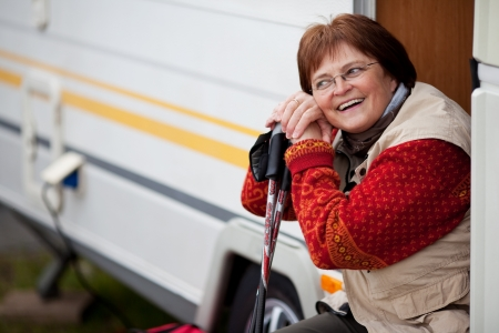 motorhome: Portrait of smiling mature woman holding hiking poles while sitting at caravan doorway Stock Photo