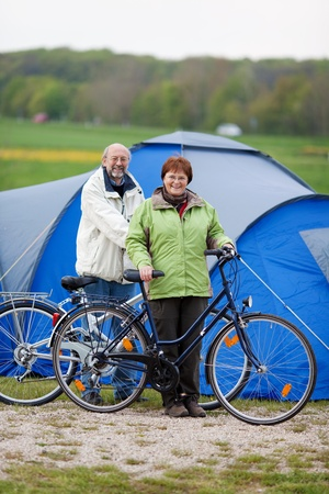 recreational vehicle: Portrait of happy couple with bicycles standing against tent