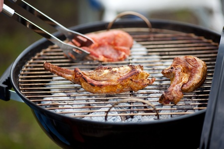 unhealthful: Closeup of meat and tongs on barbecue