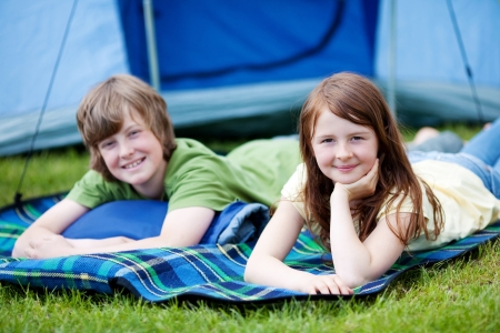Portrait of young brother and sister lying on blanket with tent in background at forest photo