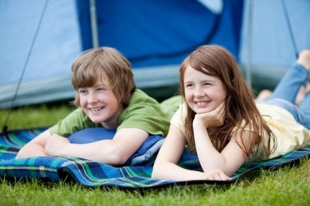 Portrait of two kids lying on blanket with tent in background photo