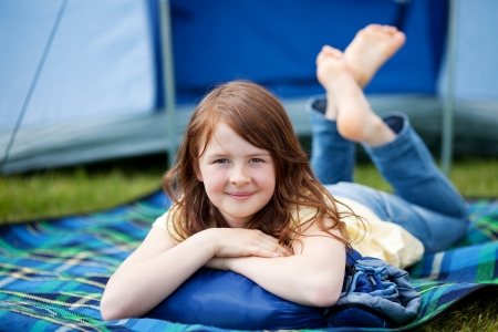 campsite: Portrait of young girl lying on blanket with tent in background