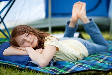 Young girl sleeping on blanket with tent in background photo