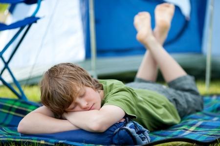 sleeping bag: Young boy sleeping on sleeping bag with tent in background