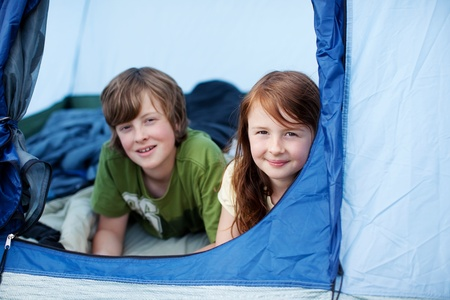 Portrait of young kids lying in tent photo
