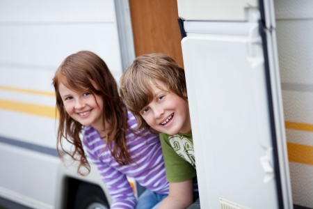 Portrait of playful boy and girl sitting at caravan entrance photo