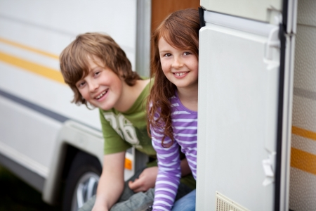 Young brother and sister sitting in a doorway of RV photo