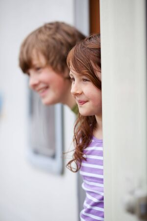 Young brother and sister looking away while at doorway of RV photo