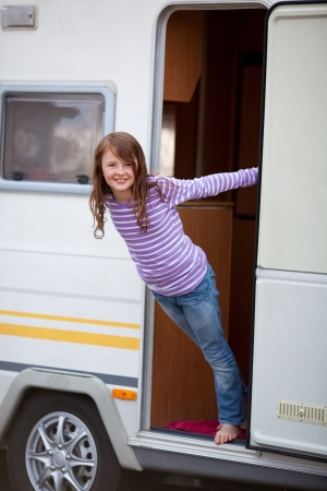 Portrait of playful cute girl standing at caravan entrance photo