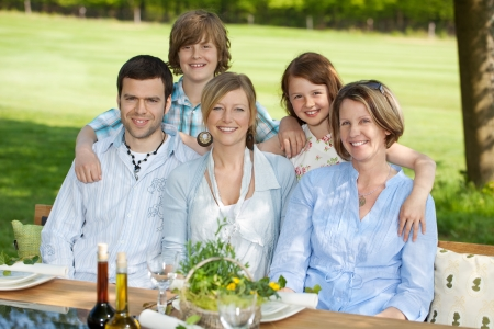 Portrait of happy family smiling together at dining table Stock Photo - 21302038