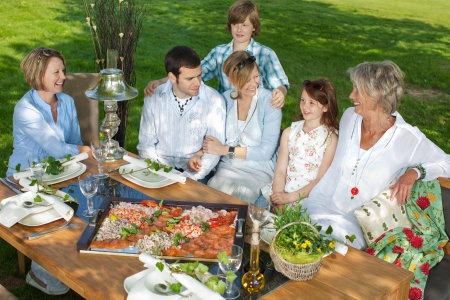 happy family sitting together at dining table in the garden Stock Photo - 21302053