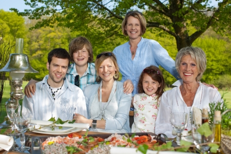 Group portrait of happy family smiling together at dining table photo