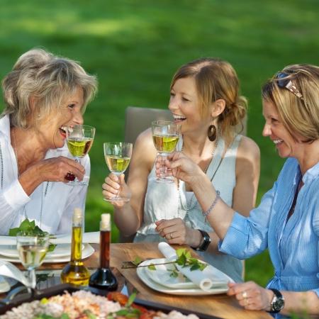familia cenando: Familia feliz que tuesta el vino blanco en la mesa de comedor en el jard�n Foto de archivo