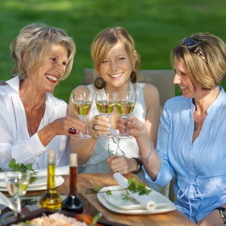 mujeres maduras: mujeres felices diciendo brindar con vino blanco en la fiesta en el jardín