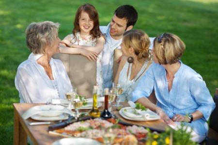 fiesta familiar: abuela feliz con su familia sentado al aire libre