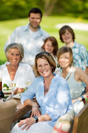 happy family sitting at table and having a garden party Stock Photo - 21302078