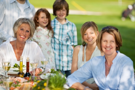happy family having dinner in the garden in summer photo