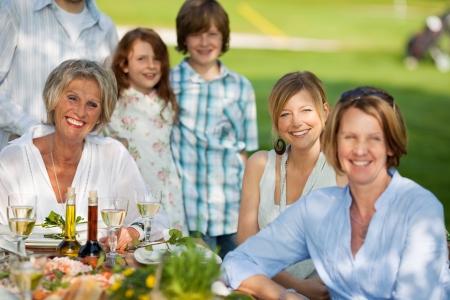 glückliche Familie, die Abendessen im Garten im Sommer