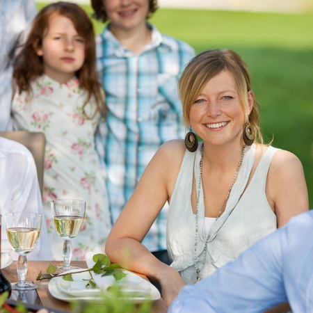 Portrait of happy young woman with family sitting in lawn photo