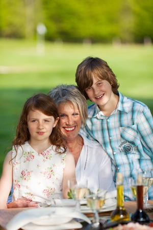 Portrait of happy grandmother and grandchildren at dining table in lawn Stock Photo - 21302115