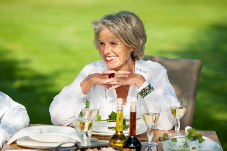 Happy senior woman with hands clasped looking away at dining table in lawn photo