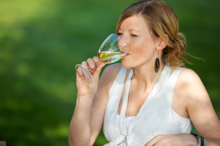 Young woman drinking white wine in lawn Stock Photo