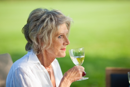 senior woman enjoying a glass of wine sitting in the garden photo