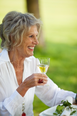 Happy senior woman looking away while holding wineglass in lawn Stock Photo - 21302123