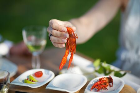 woman picking up crayfish at dinner outdoors
