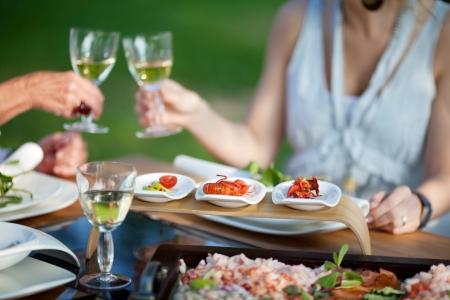 familia cenando: la gente en la mesa de comedor en el jard�n brindando con vino
