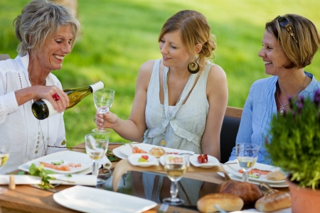 lawn party: Senior woman pouring wine in glass for daughter at dining table in lawn Stock Photo