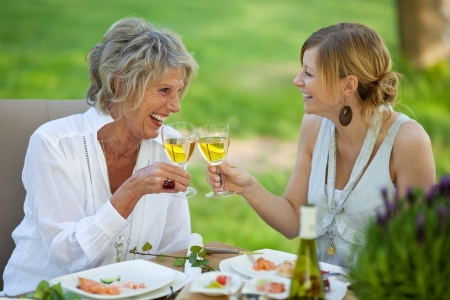 mediterranean style: Happy mother and daughter toasting white wine at dining table in lawn Stock Photo