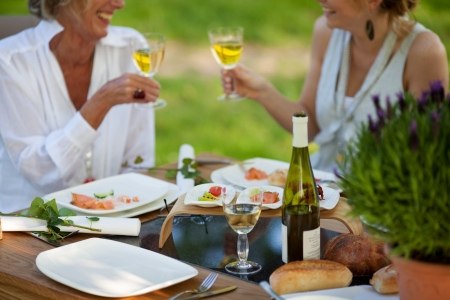 mediterranean style: two women saying cheers at dining table outdoors