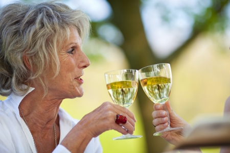 smiling elderly woman saying cheers with white wine