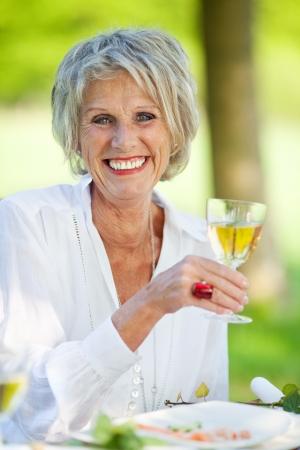 modern senior woman enjoying white wine in the garden Stock Photo - 21287167