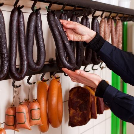 arranging: Closeup of female butcher arranging sausages on hooks