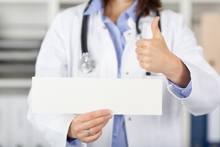 Midsection of female doctor holding blank paper while gesturing thumbs up in clinic photo