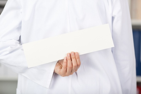 Rear view of mid adult female doctor holding blank label in clinic photo