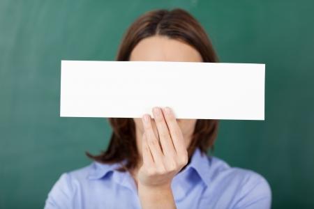 avergonzado: Primer plano de maestro que sostiene el papel en blanco sobre la pizarra Foto de archivo