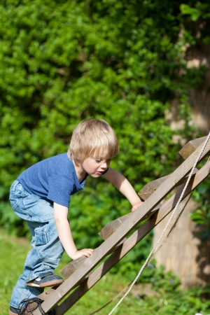Cute boy climbing wooden ladder in playground photo
