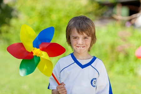 Portrait of little boy holding pinwheel in yard photo