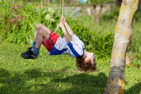Little boy having a ball on a swing in the park photo