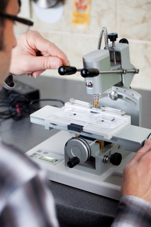 rimless: Closeup of an optician drilling rimless glasses in workshop Stock Photo