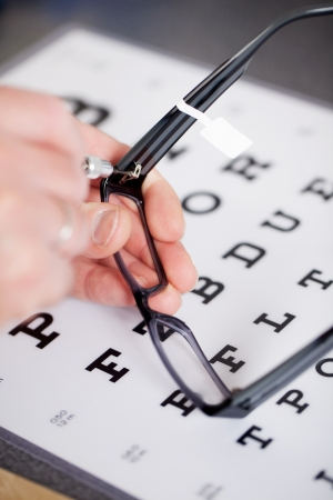 optical instrument: optician fixing frame with snellen chart in background Stock Photo