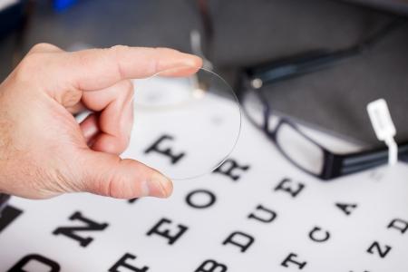 Gros plan de l'objectif de maintien de la main de opticien contre Snellen Banque d'images - 21286807