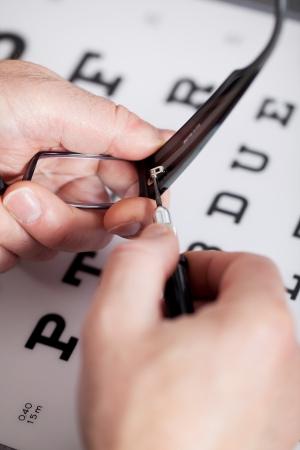vision repair: Closeup of opticians hands repairing glasses