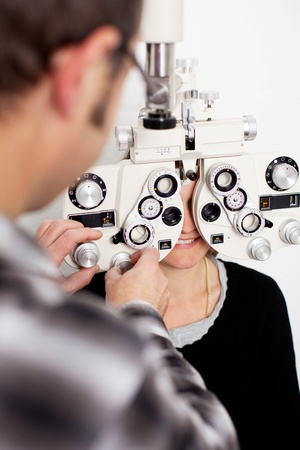 eye exam: doctor and female patient in eye clinic with measurement tool Stock Photo