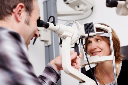Closeup of an mature optician testing patients eyes in examination room photo