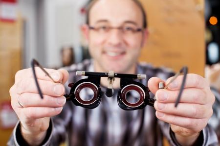 Closeup portrait of mature optician holding eye test glasses Imagens