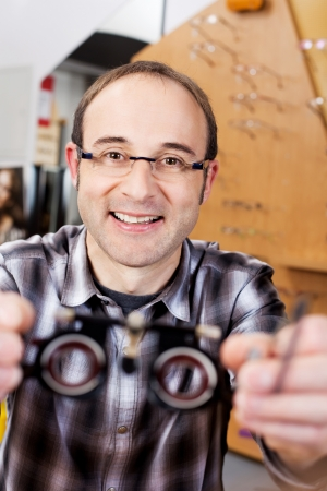 confident optician holding test lenses in a shop photo